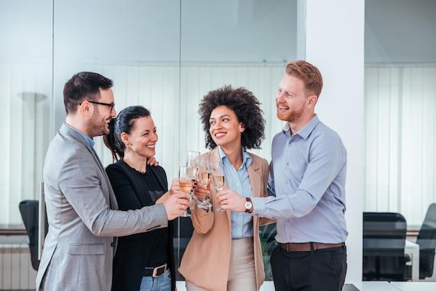 Groupe de gens d'affaires tinter leurs flûtes de champagne comme un succès.