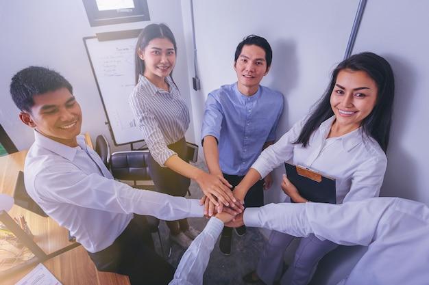 Groupe de gens d'affaires unissent leurs efforts au bureau.