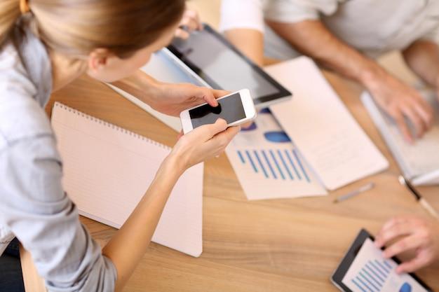 Groupe de gens d'affaires utilisant des appareils électroniques au travail
