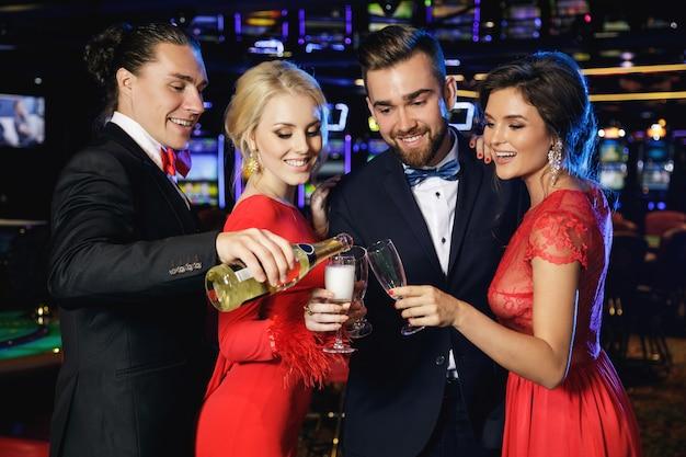 Groupe de gens heureux de boire du vin mousseux dans le casino
