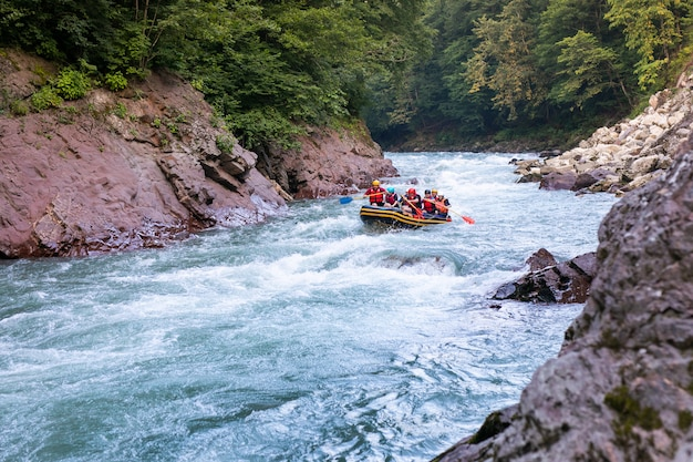 Groupe de gens heureux avec guide rafting et aviron sur rivière.