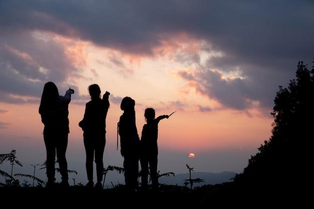 Groupe de gens heureux jouant au coucher du soleil de l'été dans la nature