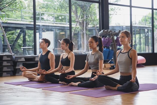Groupe de gens de race mixte pratiquant le yoga méditant ensemble pour un mode de vie sain dans un club de remise en forme