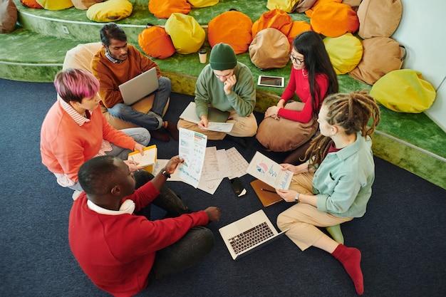 Groupe de gestionnaires financiers interculturels faisant un remue-méninges et discutant de documents avec des graphiques et des graphiques lors d'une réunion de travail sur le sol