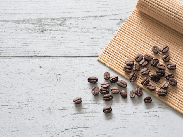 Groupe de graines de café sur la vue de dessus de plaque de bambou sur l'espace de table en bois