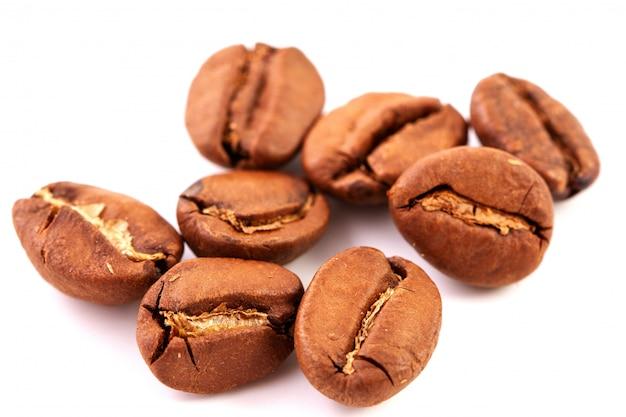 Groupe de grains de café torréfiés isolés, gros plan.