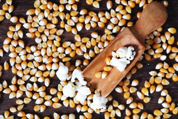 Groupe de grains de maïs crus jaunes maïs sucré. graines de grains ingrédient grain de maïs doré. fond de pop-corn mûr de table en bois.