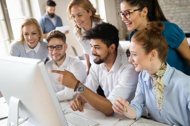 Groupe heureux d'étudiants apprenant le génie logiciel et les affaires pendant la présentation