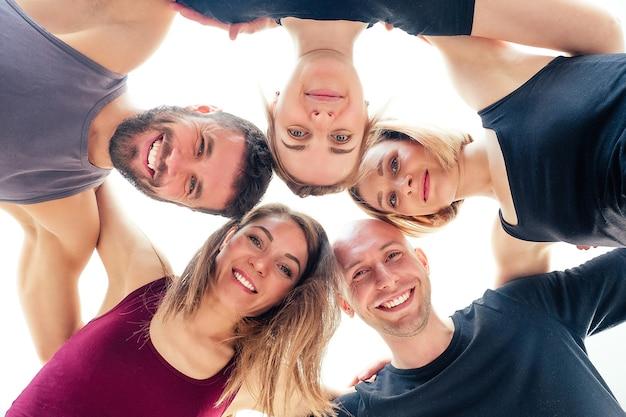 Un groupe heureux d'hommes et de femmes pratiquant le yoga en studio. groupes de méditation, cours de yoga de la communication. le concept de méditation de groupe et de travail d'équipe. entraîneur et étudiants en cercle.