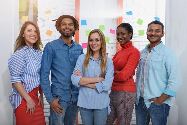 Un groupe heureux de partenaires commerciaux travaille au bureau