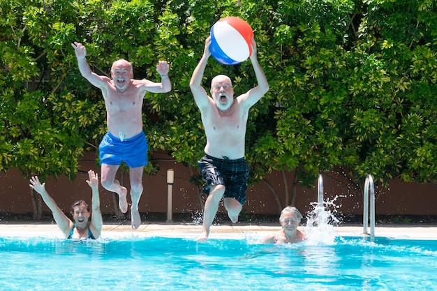 Groupe heureux de personnes mûres appréciant l'été et la piscine sautant et jouant avec le bal