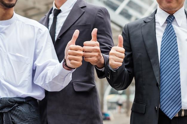 Groupe d'homme d'affaires montrant les pouces vers le haut de succès