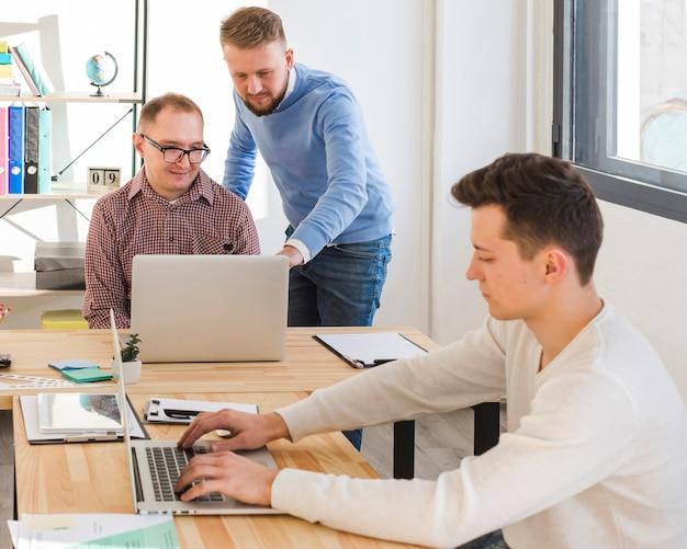 Groupe d'hommes adultes ensemble au bureau