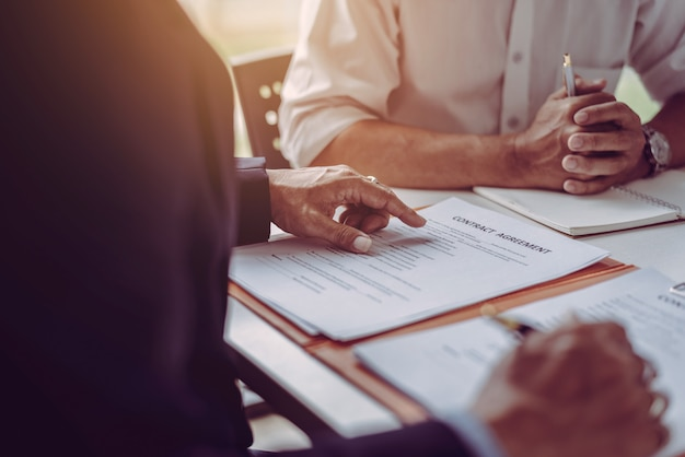 Groupe d'hommes d'affaires asiatiques d'âge moyen et d'avocats discutant et signant un contrat.