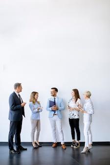 Groupe d'hommes d'affaires debout près du mur du bureau