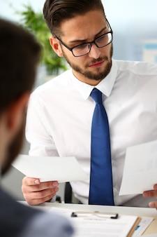 Groupe d'hommes d'affaires avec graphique financier dans le bras résoudre et discuter du problème