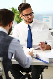 Groupe d'hommes d'affaires avec graphique financier et stylo argent dans le bras résoudre et discuter du problème avec le portrait d'un collègue. examen de la situation au conseil d'administration du conseil en vente d'emploi