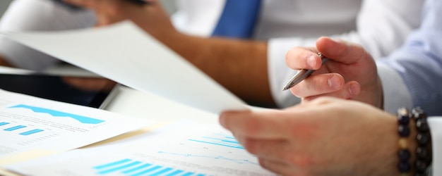 Groupe d'hommes d'affaires avec graphique financier et stylo argenté