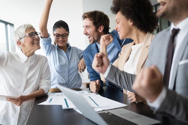 Groupe d'hommes d'affaires heureux et prospères au travail au bureau