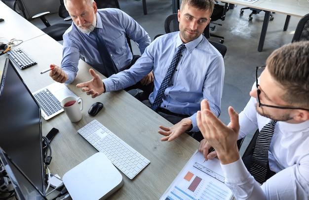 Groupe d'hommes d'affaires modernes en tenue de soirée analysant les données boursières tout en travaillant au bureau.