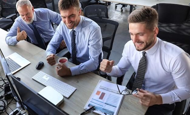 Groupe d'hommes d'affaires modernes en tenue de soirée souriant et faisant des gestes tout en travaillant au bureau.