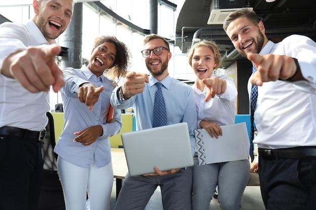 Groupe d'hommes d'affaires modernes vous pointant du doigt.