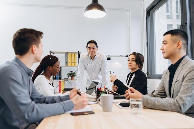 Groupe d'hommes d'affaires multiculturels écoutant leur discours de patron, gestionnaire de l'homme asiatique parlant à son équipe