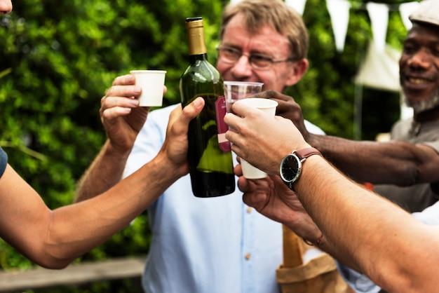 Groupe d'hommes buvant du vin rouge local ensemble