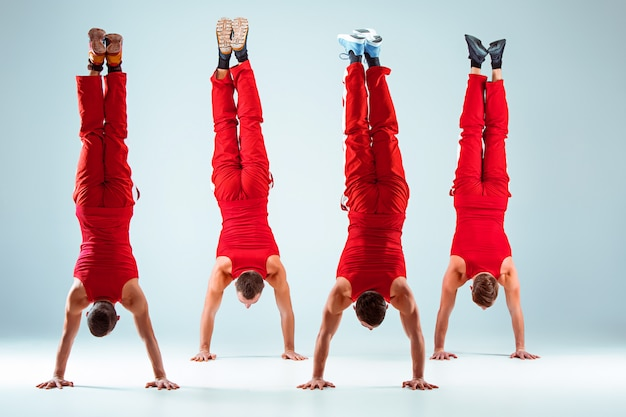 Groupe d'hommes caucasiens acrobatiques de gymnastique en équilibre posent