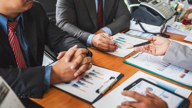 Groupe d'hommes entrepreneurs discutant d'un projet de gestion lors d'une collaboration