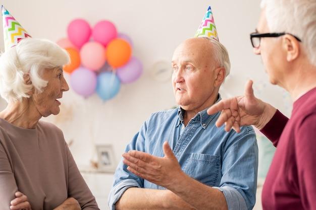 Groupe d'hommes et de femmes âgés discutant de quelque chose à la fête d'anniversaire à la maison
