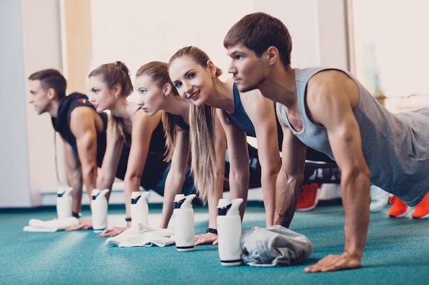 Groupe hommes et femmes effectue un exercice physique.
