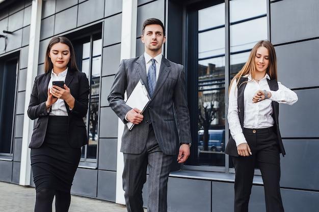 Groupe d'hommes et de femmes heureux d'utiliser un téléphone intelligent pour discuter de l'arrière-plan d'un immeuble de bureaux moderne.