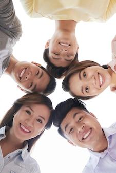 Groupe d'hommes et de femmes souriants regardant quelque chose ensemble, tiré d'en bas