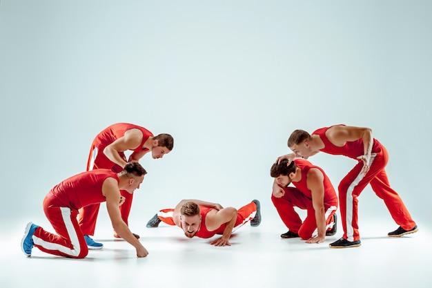 Le groupe d'hommes de race blanche acrobatique gymnastique