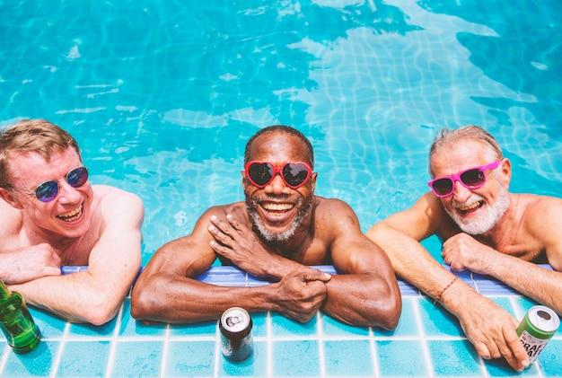 Groupe d'hommes seniors divers appréciant la piscine ensemble