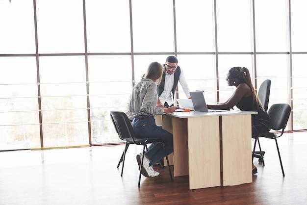 Groupe d'indépendants travaillant dans le bureau spacieux avec de grandes fenêtres