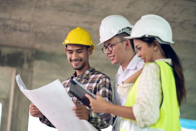 Groupe d'ingénieur architecte et officier contremaître se réunissant sur le plan de travail de construction sur chantier