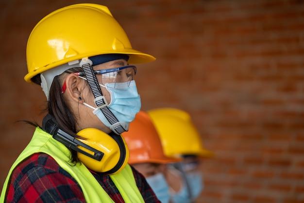 Un groupe d'ingénieurs professionnels porte des masques protecteurs pour la protection contre la maladie à coronavirus 2019 (covid-19) dans une usine industrielle de machines, le coronavirus est devenu une urgence mondiale.