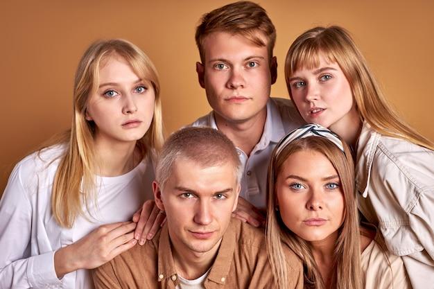 Groupe inhabituel de jeunes extraordinaires posant dans des vêtements à la mode, des modèles caucasiens regardent avec confiance la caméra isolée en studio
