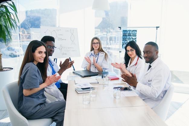 Groupe international de jeunes médecins professionnels applaudissent et sourient lors d'une conférence médicale dans une clinique moderne