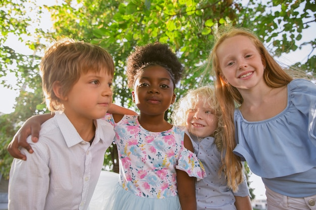 Groupe interracial d'enfants posant ensemble au parc