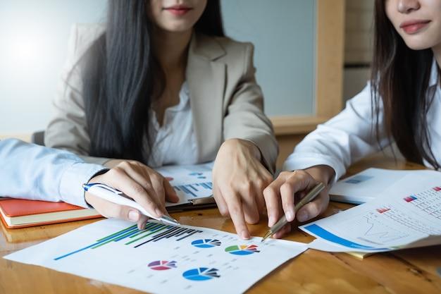 Groupe d'investisseurs diversifié brainstorming et pointant sur un ordinateur portable sur le bureau en bois.