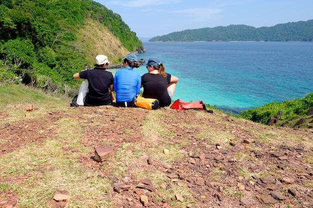 Groupe de jeune fille s'asseoir sur une falaise, les montagnes et les paysages de mer avec un ciel bleu