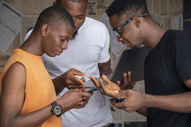 Groupe de jeunes africains partageant du contenu via leur ordinateur portable et leurs téléphones