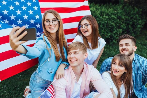 Un groupe de jeunes américains faisant du selfie avec le drapeau américain.