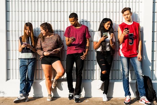 Groupe de jeunes amis adolescents se détendre ensemble en utilisant le concept de médias sociaux smartphone