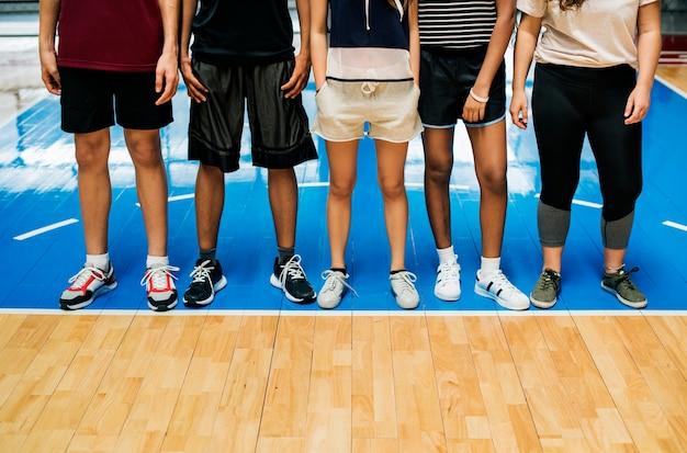 Groupe de jeunes amis adolescents sur un terrain de basket debout dans une rangée