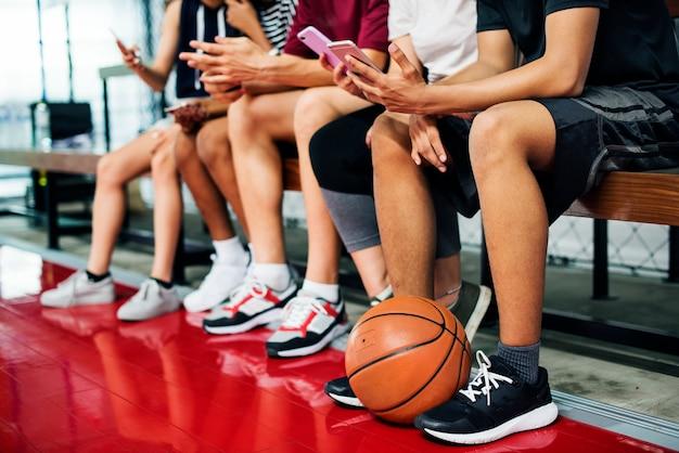 Groupe de jeunes amis adolescents sur un terrain de basket relaxant à l'aide de smartphone