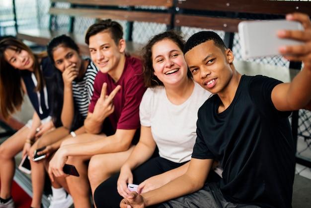 Groupe de jeunes amis adolescents sur un terrain de basket relaxant prenant un selfie